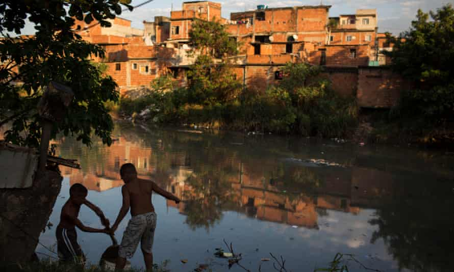 Youth play alongside a polluted river in the Manguinhos slum complex in Rio de Janeiro.