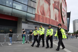 Police officers walk past people queuing to receive a their Covid-19 vaccine at the Emirates Stadium in London, UK