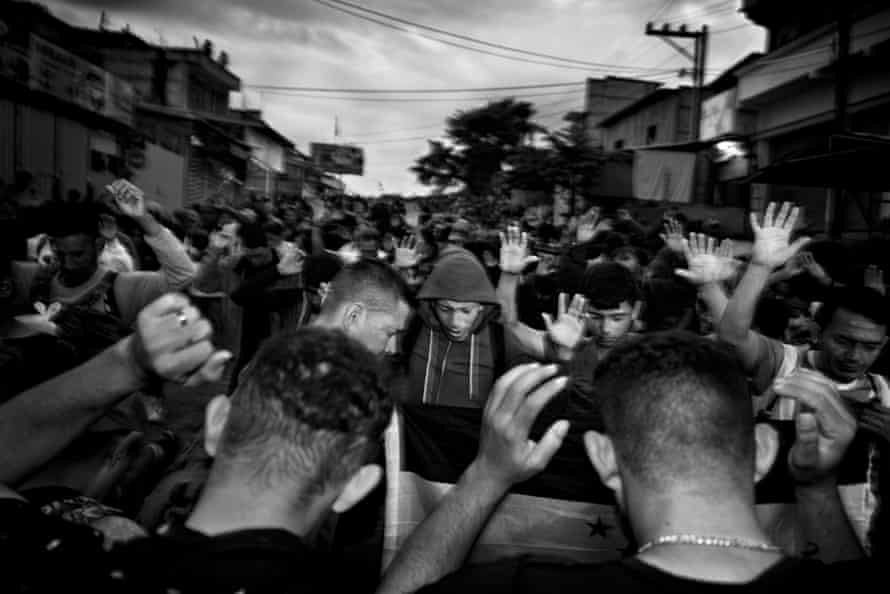 Early in the morning in El Ceibo, Guatemala, before starting their journey, men pray for a safe passage north to the US