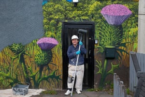 Robin Rankin paints over a mural of thistles and Loch Lomond at Balloch.