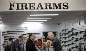 Sales associate Mike Conway, right, shows Paul Angulo guns at Bullseye Sport gun shop in Riverside, California, on 9 December 2015. The state has strict policies on gun control.