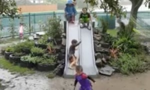 A still from the video showing children gleefully leaping down the slide into a muddy puddle in the middle of a rainstorm.
