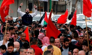 Members of the Popular Front for the Liberation of Palestine wave the group's flag during Sajid Muzher's funeral.