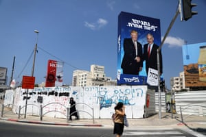 Pedestrians walk next to a Likud party election campaign banner in Bnei Brak, Israel in September.