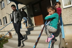 Syrian refugee Mohamed Ali Hussein, left, leaves the shelter as eight-year-old Chechen Alina Dzhankayeva, in turqoise, hangs out on the steps
