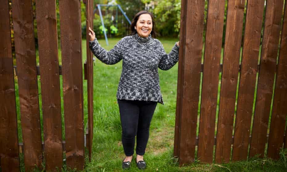 Pragya Agarwal in her garden, looking through a gap in the fence