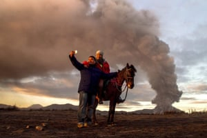 <strong>Probolinggo, Indonesia</strong><br>Tourists take a selfie as Mount Bromo spews volcanic material and ash into the air. The volcano is on the second highest alert level as its activity has increased in the last two months