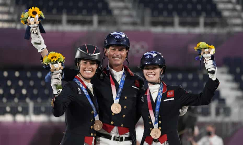 Charlotte Dujardin (left), Carl Hester and Charlotte Fry stand on the podium after receiving the bronze medal for the dressage team event.