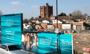 A construction site behind blue advertising hoardings