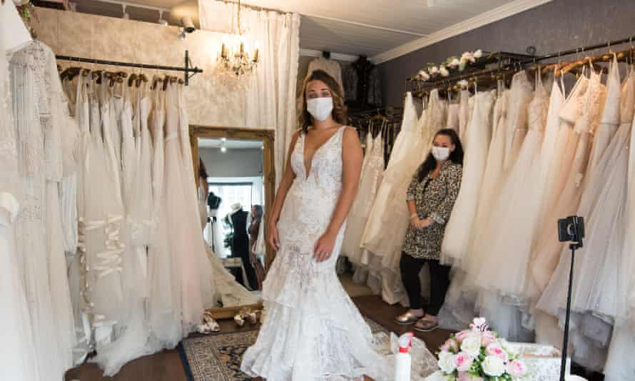 A future bride wears a face mask as she tries on wedding dresses in Blush bridal boutique on July 4, 2020 in Leigh-on-Sea, England.
