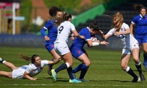 England's fly-half Helena Rowlandgrabs hold of the shirt of France's centre Carla Neisen.