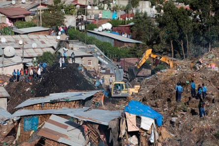 Excavators move earth as rescuers work at the site of the landslide