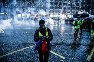 Paris, France: Gilets jaunes protesters stand near teargas on the Champs-Élysées