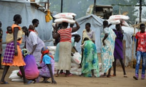 Women in Juba carry flour sacks distributed by an aid agency in August 2014.