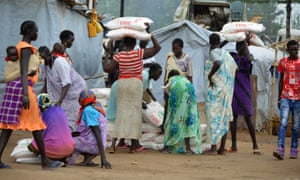 Women carry maize flour sacks during a food distribution to refugees and displaced people in Juba, South Sudan's capital.