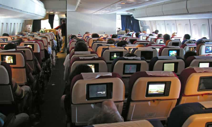 An aircraft cabin with TV screens