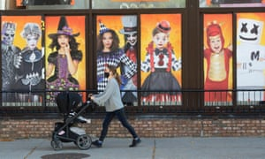 A woman pushing a pram past a colourful shop window displaying Halloween items