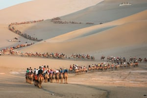 Gansi, China: Tourists ride camels in the desert in Dunhuang