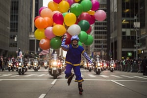 A performer carries balloons across Sixth Avenue