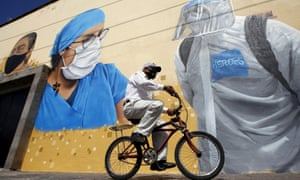A man rides a bicycle in front of a mural, painted by city hall workers as part of the Zapopart programme – a tribute to essential workers who have cared for citizens during the Covid-19 pandemic in the state of Jalisco, Mexico.