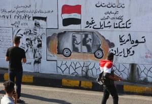 Iraqis walk past graffiti hailing Iraq's tuk-tuk drivers who have been helping the protesters reading 'our Tuk-tuk drivers are in the fire, they help others … they are better than America and Iran together.' The drivers of the motorised rickshaws, typically seen in poorer parts of the capital, have become the unofficial heroes of the protest movement.