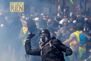 Paris, France. Tear gas floats around masked protesters during clashes before the start of the traditional May Day labour union march