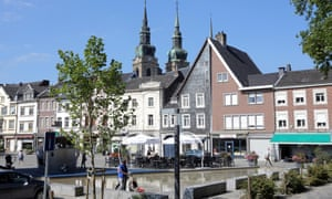 A man walks with his child through the centre of Eupen