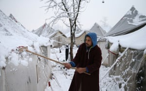 Bihać, Bosnia and Herzegovina. A man cleans snow from his tent at a makeshift migrant camp in the forest