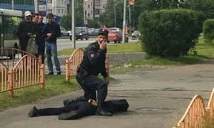 A Russian policeman stands over the suspected attacker in Surgut, Siberia.
