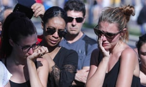 People react near the scene of the attack in Nice.