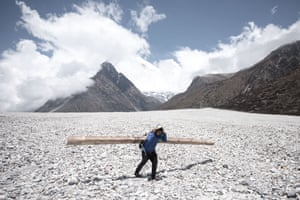 A volunteer worker carries a wooden beam across scree formed by one of the huge landslides near Kyanjin Gompa