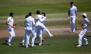 Bowler and wicketkeeper celebrate their teamwork.