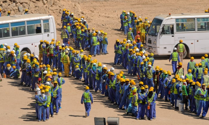 Foreign construction workers queue for buses back to their accommodation camp in Doha.