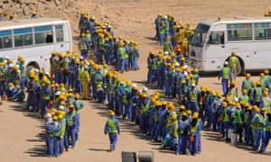 Construction workers queue for buses back to their accommodation camp in Doha, Qatar.