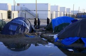 Migrants walk among tents