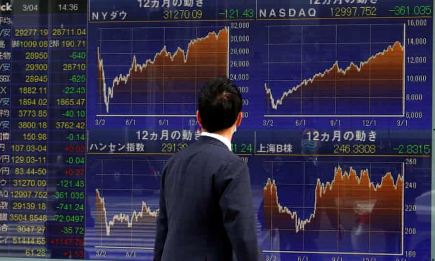 A man walks past a Nikkei stock index at a brokerage in Tokyo