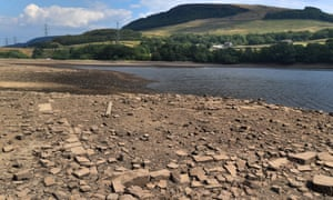 The remains of an old building pre-dating the reservoir are seen on the dried-out reservoir bed due to low water levels in Bottoms Reservoir, near Tintwistle, Derbyshire, on 5 July.