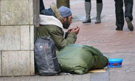 A homeless man lights a cigarette