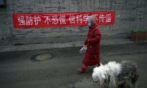 """A woman walking a dog in Beijing, in front of a banner reading """"Strengthen self-protection, do not panic, believe in science, do not spread rumours""""."""