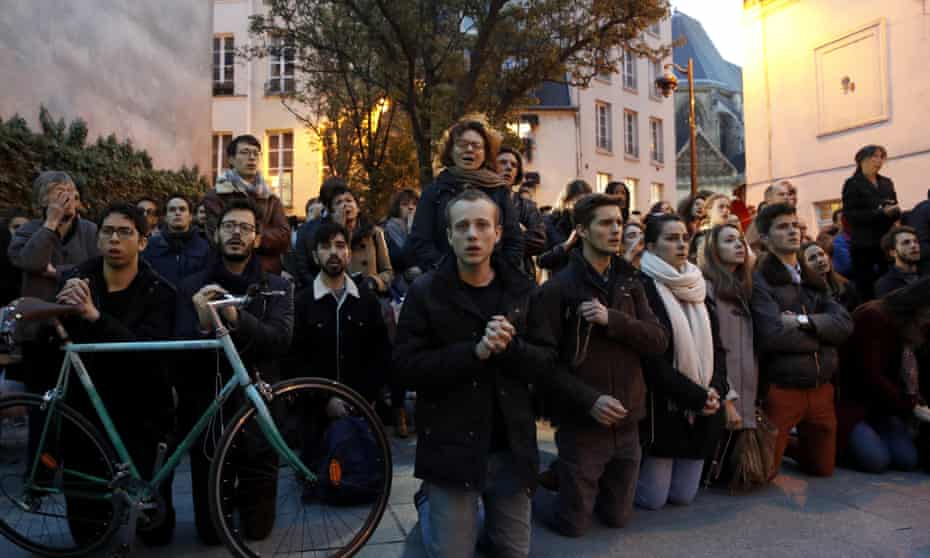 Parisians kneel in prayer as the 'soul of the nation' burns.