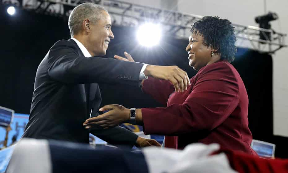 Barack Obama and Stacey Abrams embrace, under the bright lights at Morehouse college in Atlanta.