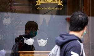 Designer face masks on display in a shirtmaker's shop window in Manchester, UK.