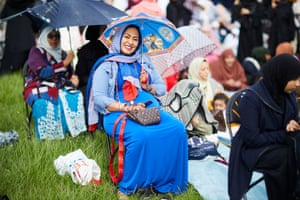 A woman smiles underneath an umbrella at an Eid event in Manchester, England