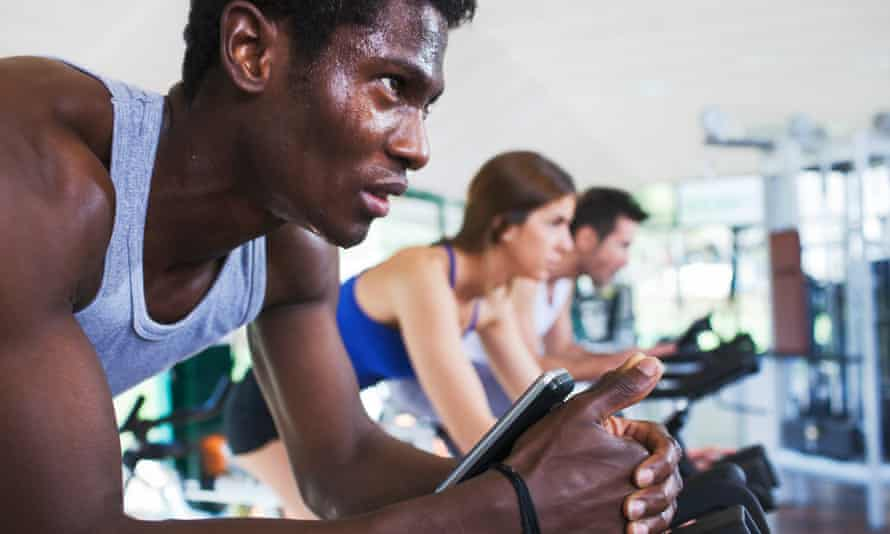 Three young adults working hard in a spinning class