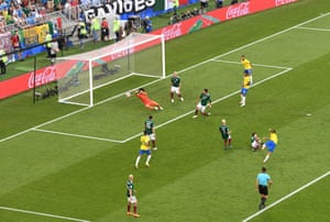 Mexico's keeper Guillermo Ochoa thwarts Philippe Coutinho.