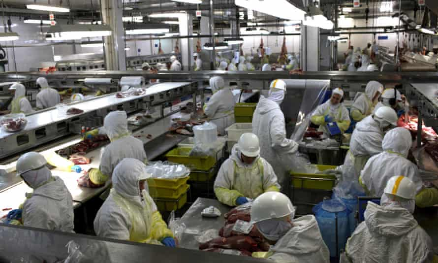 Workers process meat at the Minerva SA processing plant in Barretos, Brazil
