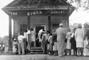 African American voters, able to vote for the first time in rural Wilcox County, Alabama, line up in front of a polling station at The Sugar Shack, a local general store. After the passage of the federal voting rights law in 1965, there were almost twice as many black voters than whites.