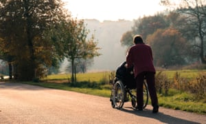 A carer pushes a man in a wheelchair during a walk together in a park.