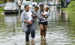 Jalana Furlough carries her son Drew Furlough as Terrian Jones carries Chance Furlough in New Orleans after flooding on Wednesday.