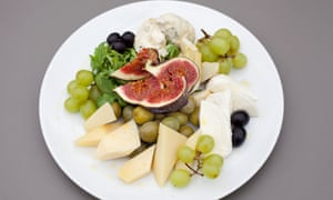 A cheese platter with gorgonzola, toma and mozzarella, a scattering of green grapes and fig pieces on the top